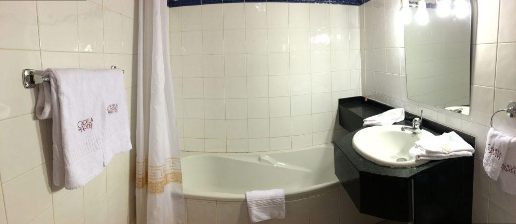 Salle de bain avec baignoire, sèche cheveux, serviettes et articles de toilettes gratuits